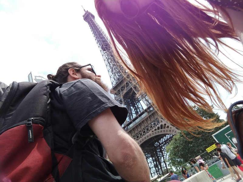 Jaydson em viagem, na frente da torre Eiffel